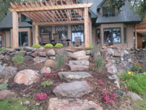 Beautiful Natural Landscaping- Pergola, Wood Look Paver, Boulder Walls, Stone Steps